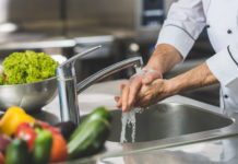 cropped image of chef washing hands at restaurant kitchen